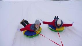 Τα κορίτσια εφήβων κυλούν στο γύρο ελκήθρων κατά μήκος του λευκού σαν το χιόνι δρόμου το χειμώνα Οι φίλες οδηγούν το πιατάκι χιον φιλμ μικρού μήκους