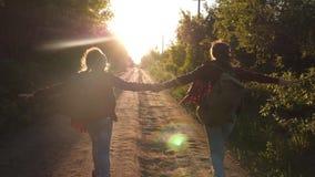 Τα κορίτσια εφήβων ταξιδεύουν και κρατούν τα χέρια ταξιδιώτες παιδιών Κορίτσι οδοιπόρων ευτυχείς ταξιδιώτες κοριτσιών με τα σακίδ απόθεμα βίντεο