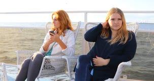 Τα κορίτσια κάθονται στις καρέκλες στο κατάστρωμα του πλοίου απόθεμα βίντεο