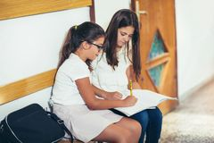 Τα κορίτσια κάθονται στο σχολείο διαδρόμων Στοκ εικόνες με δικαίωμα ελεύθερης χρήσης