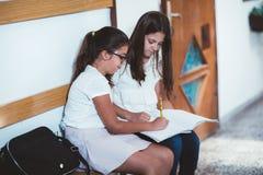 Τα κορίτσια κάθονται στο σχολείο διαδρόμων Στοκ Εικόνες