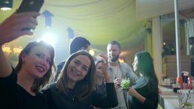 Τα κορίτσια κάνουν τη μόνη φωτογραφία στη συσκευή πίσω από το μετρητή φραγμών στο νυχτερινό κέντρο διασκέδασης στο υπόβαθρο των φ απόθεμα βίντεο