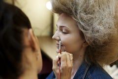 Τα κορίτσια με έναν πολύβλαστο hairstyle καλλιτέχνη σύνθεσης κάνουν τη σύνθεση στοκ εικόνα με δικαίωμα ελεύθερης χρήσης