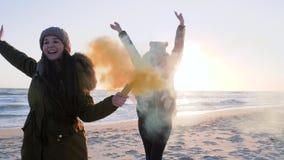 Τα κορίτσια με το ζωηρόχρωμο καπνό τρέχουν και έχουν τη διασκέδαση στην παραλία κοντά στη θάλασσα απόθεμα βίντεο