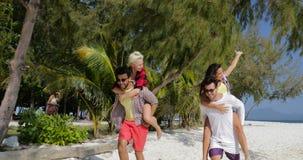 Τα κορίτσια οδηγούν τα άτομα πίσω στην παραλία, ζεύγος δύο που έχει τους ευτυχείς χαμογελώντας τουρίστες διασκέδασης στις καλοκαι απόθεμα βίντεο