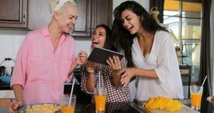 Τα κορίτσια ομαδοποιούν χρήσης ταμπλετών υπολογιστών τις ομιλούσες κουδουνίσματος γυναίκες προγευμάτων χυμού μαγειρεύοντας στο σύ φιλμ μικρού μήκους