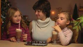 Τα κορίτσια πίνουν την καυτή σοκολάτα μέσω ενός αχύρου φιλμ μικρού μήκους
