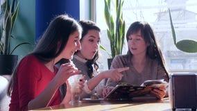 Τα κορίτσια πίνουν τον καφέ και κοιτάζουν βιαστικά τη συνεδρίαση επιλογών στον πίνακα στον καφέ φιλμ μικρού μήκους