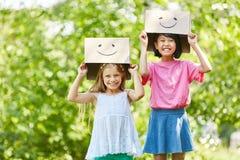 Τα κορίτσια παίζουν με τα αστεία χρωματισμένα κουτιά από χαρτόνι Στοκ Εικόνα