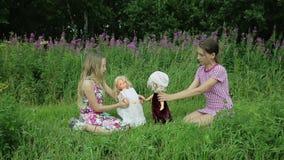 Τα κορίτσια παίζουν με τις κούκλες στη χλόη φιλμ μικρού μήκους
