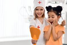 Τα κορίτσια παιδιών παίζουν τον οδοντίατρο και τον ευτυχή ασθενή στο οδοντικό γραφείο Ο ασθενής είναι ευχαριστημένος από τα υγιή  στοκ φωτογραφίες