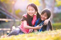 Τα κορίτσια παιδιών αγκαλιάζουν στο πράσινο πάρκο χλόης Στοκ Εικόνα