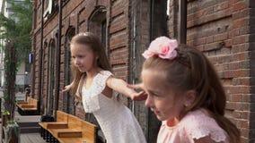 Τα κορίτσια περιμένουν τους φίλους στο μεγάλο κτήριο τούβλου Τα καλά μικρά κορίτσια θέτουν για τη κάμερα φιλμ μικρού μήκους
