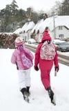 Τα κορίτσια περπατούν μέσω του χιονισμένου χωριού στοκ φωτογραφία