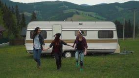 Τα κορίτσια περπατούν τα χέρια εκμετάλλευσης κοντά σε ένα ρυμουλκό στα βουνά φιλμ μικρού μήκους