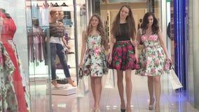 Τα κορίτσια πηγαίνουν μετά από να ψωνίσουν στη λεωφόρο αγορών με τις τσάντες αγορών φιλμ μικρού μήκους