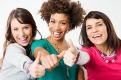 Τα κορίτσια που εμφανίζουν αντίχειρα υπογράφουν επάνω Στοκ Φωτογραφίες