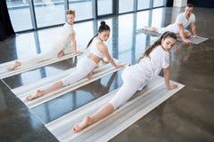 Τα κορίτσια που κάνουν τη γιόγκα μισό-περιστεριών θέτουν με τον εκπαιδευτικό στο εσωτερικό Στοκ φωτογραφία με δικαίωμα ελεύθερης χρήσης