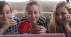 Τα κορίτσια που προσέχουν τα μέσα ικανοποιούν στο lap-top ενώ έχοντας τα τρόφιμα και το ποτό απόθεμα βίντεο