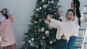 Τα κορίτσια που χύνονται τη σαμπάνια κοντά σε ένα χριστουγεννιάτικο δέντρο φιλμ μικρού μήκους