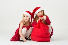 Τα κορίτσια σε ένα κόκκινο ντύνουν στη συνεδρίαση Άγιου Βασίλη κουδουνιών Στοκ φωτογραφία με δικαίωμα ελεύθερης χρήσης