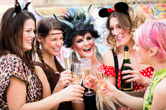 Τα κορίτσια σε καρναβάλι παρελαύνουν τα clinking γυαλιά με τη σαμπάνια στοκ εικόνες