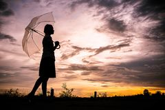 Τα κορίτσια σκιαγραφούν το ύφος περπατώντας μόνους υπαίθριο και την ομπρέλα μέσα στοκ εικόνες