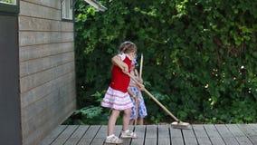 Τα κορίτσια σκουπίζουν το πάτωμα απόθεμα βίντεο