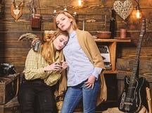 Τα κορίτσια στα χαλαρωμένα πρόσωπα κρατούν τις μεταλλικές κούπες, απολαμβάνουν το coziness με τα ποτά Οι φίλοι περνούν το εκφραστ στοκ φωτογραφία με δικαίωμα ελεύθερης χρήσης