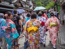 Τα κορίτσια στο κιμονό περπατούν επάνω μια παραδοσιακή οδό Στοκ Φωτογραφία