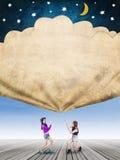 Τα κορίτσια τραβούν ένα έμβλημα με τα αστέρια και το φεγγάρι Στοκ Εικόνες