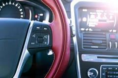 Τα κουμπιά ελέγχου MEDIA στο κόκκινο τιμόνι στο μαύρο δέρμα με τον υπολογιστή ελέγχουν, σύγχρονο εσωτερικό αυτοκινήτων Μαλακός φω Στοκ Εικόνες