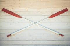 Τα κουπιά κανό κρεμούν στον άσπρο ξύλινο τοίχο Copyspace στοκ φωτογραφία