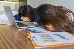 Τα κουρασμένα κορίτσια βάζουν το πρόσωπό τους κάτω στο γραφείο Στοκ Εικόνες