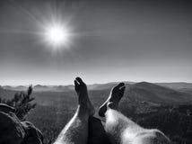 Τα κουρασμένα πόδια παίρνουν το υπόλοιπο στην αιχμή του βράχου Ταξίδι στον καυτό θερινό καιρό Στοκ φωτογραφία με δικαίωμα ελεύθερης χρήσης