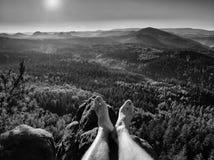 Τα κουρασμένα πόδια παίρνουν το υπόλοιπο στην αιχμή του βράχου Ταξίδι στον καυτό θερινό καιρό Στοκ εικόνες με δικαίωμα ελεύθερης χρήσης