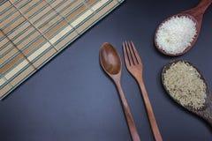 Τα κουτάλια, τα δίκρανα και οι κουτάλες βάζουν το ρύζι με jasmine το ρύζι Στοκ Φωτογραφίες