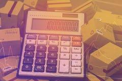 Τα κουτιά από χαρτόνι και ένας υπολογιστής με τους αριθμούς εμφανίζονται Τεχνικό γ στοκ εικόνα