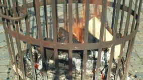 Τα κούτσουρα και το ξύλο φλογών πυρκαγιάς με το παραδοσιακό βαρέλι χοανών σιδήρου, άνθρωποι περπατούν γύρω στο τετραγωνικό, λαϊκό φιλμ μικρού μήκους
