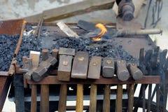 Τα κρεμώντας σφυριά σφυρηλατούν το κάρρο από έναν σιδηρουργό Στοκ Εικόνες