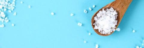 Τα κρύσταλλα της μεγάλης θάλασσας αλατίζουν σε ένα ξύλινο κουτάλι σε έναν μπλε πίνακα στοκ φωτογραφίες με δικαίωμα ελεύθερης χρήσης