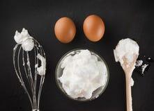 Τα κτυπημένα λευκά αυγών για την κρέμα σε ένα κύπελλο γυαλιού, χτυπούν ελαφρά και το ξύλινο s στοκ φωτογραφία με δικαίωμα ελεύθερης χρήσης