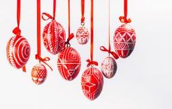 Τα κόκκινα αυγά Πάσχας με το λαϊκό ουκρανικό σχέδιο κρεμούν στις κόκκινες κορδέλλες από τη αριστερή πλευρά στο άσπρο υπόβαθρο Ουκ Στοκ εικόνα με δικαίωμα ελεύθερης χρήσης
