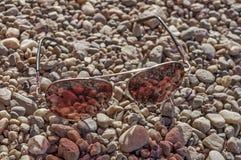 Τα κόκκινα γυαλιά ήλιων σε μια ακτή κλείνουν Στοκ εικόνες με δικαίωμα ελεύθερης χρήσης