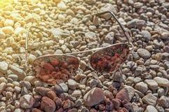 Τα κόκκινα γυαλιά ήλιων σε μια ακτή κλείνουν Στοκ Φωτογραφίες