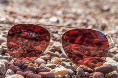 Τα κόκκινα γυαλιά ήλιων σε μια ακτή κλείνουν Στοκ Εικόνα