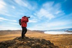 Τα κόκκινα ενδύματα ένδυσης φωτογράφων παίρνουν το βουνό και τη λίμνη baikal φωτογραφιών στην ημέρα στη Σιβηρία, Ρωσία στοκ εικόνες