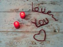 Τα κόκκινα κεριά και σας αγαπούν επιστολές στο ξύλινο υπόβαθρο κλείστε επάνω Διάστημα κειμένων Δώρο για την ημέρα βαλεντίνων ` s  Στοκ Εικόνες