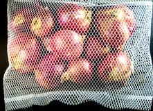 Τα κόκκινα κρεμμύδια στο πλέγμα τοποθετούν σε σάκκο και μερικά στο πάτωμα που απομονώνεται στο μαύρο backg Στοκ Εικόνες