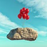 Τα κόκκινα μπαλόνια ανυψώνουν μια μεγάλη πέτρα Στοκ Εικόνες